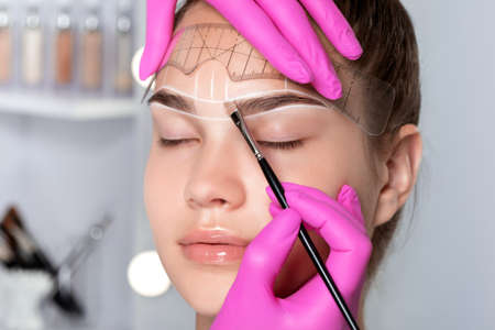 Portrait of a beautiful charming teenager girl having permanent makeup tattoo on her eyebrows. Make-up artist makes markings with white paste for eyebrow tattooing. Professional makeup.