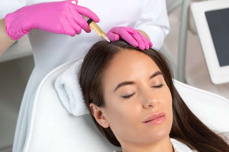 Cosmetologist does prp therapy against hair loss and anti-dandruff of a beautiful brunette woman in a beauty salon. Aesthetic cosmetology concept, hair treatment.