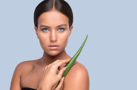 Portrait of a beautiful brunette woman with green aloe vera leaf, with naked shoulders, with healthy clean skin and fresh make-up. Aesthetic cosmetology and makeup concept.