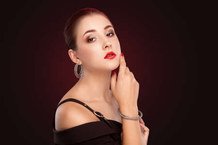 Portrait of a beautiful charming brunette woman healthy clean skin and smokey eyes make-up, red lipstick. She is wearing a black suit. Aesthetic cosmetology and makeup concept. Archivio Fotografico