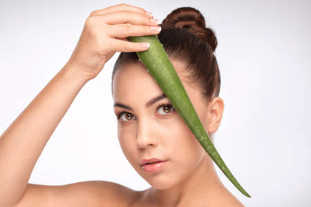 Portrait of a beautiful smiling brunette woman with green aloe vera leaf, with naked shoulders, with healthy clean skin and fresh make-up. Aesthetic cosmetology and makeup concept. Archivio Fotografico