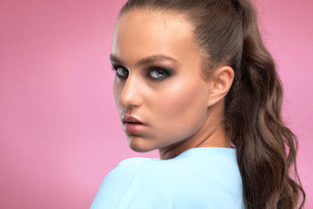 Portrait of a charming brunette woman with healthy clean skin, long hair and smokey eyes makeup. She is wearing a blue suit. The concept of aesthetic cosmetology and makeup.