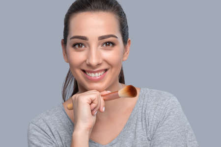 Portrait of a beautiful brunette woman with beautiful fresh makeup and healthy clean skin holding a powder brush in her hand. Professional makeup and skin care cosmetology.