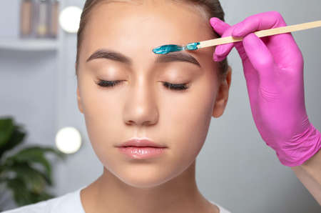 Makeup artist does facial hair removal procedure. Beautiful teenage girl with blue eyes having Permanent Make-up Tattoo on her Eyebrows. Professional makeup.