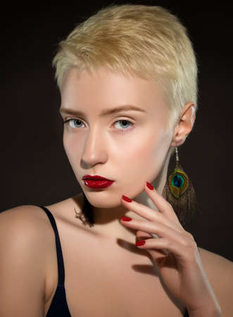 Portrait of a beautiful woman with short blonde hair, beautiful fresh make-up and red lips, with feather earrings on black background. Makeup concept. Archivio Fotografico