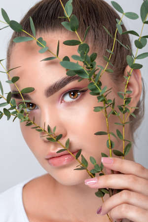 Portrait of a beautiful teenage girl with beautiful makeup and healthy clean skin. Near the face is a branch of eucalyptus. Makeup and cosmetology concept. Archivio Fotografico