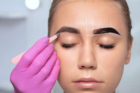 Beautiful teenage girl having Permanent Make-up Tattoo on her Eyebrows. Eyelash artist plucks eyebrows with tweezers. Professional makeup and cosmetology skin care.