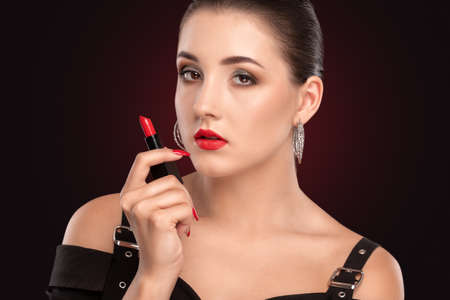 Portrait of a beautiful girl with smokey eyes makeup and healthy clean skin holding red lipstick in her hand. Professional make-up and cosmetic skin care.