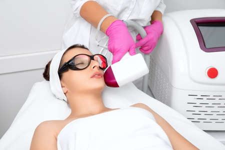 Elos epilation hair removal procedure on the face of a woman. Beautician doing laser rejuvenation in a beauty salon. Facial skin care. Hardware ipl cosmetology Archivio Fotografico