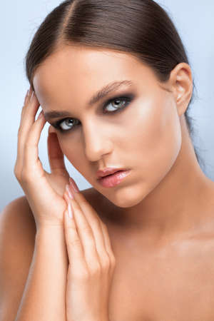 Portrait of a beautiful charming brunette woman with naked shoulders, with healthy clean skin and smokey eyes make-up. Aesthetic cosmetology and makeup concept.