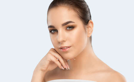 Portrait of a attractive brunette girl with healthy clean skin and fresh make-up. Aesthetic cosmetology and makeup concept.