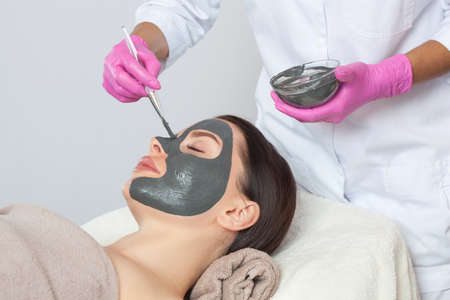 Cosmetologist does a mud mask to cleanse the skin and anti-wrinkle on the face of a beautiful woman, spa treatments and cosmetology concept. 版權商用圖片