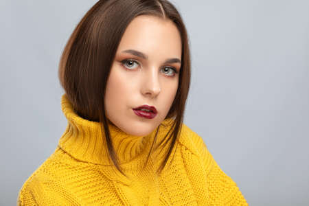 Brunette girl with beautiful makeup, with clean skin, long hair in a yellow winter sweater. New Year concept