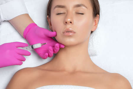 Cosmetologist makes lipolytic injections to burn fat on the chin, cheeks and neck of a woman against double chin. Female aesthetic cosmetology in a beauty salon.Cosmetology concept. Foto de archivo