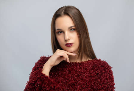 Brunette girl with beautiful makeup, with clean skin, long hair in a burgundy winter sweater. New Year concept