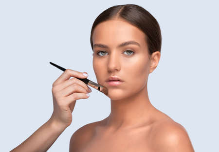 Portrait of a beautiful charming brunette teenage girl with beautiful fresh makeup and healthy clean skin.Makeup artist holds a powder brush in her hands. Professional makeup concept