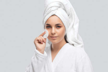 Beautiful smiling woman with clean skin holds a cotton pad. She cleanses the skin with a tonic. Cosmetology and professional skin care.