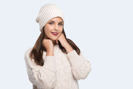 Brunette girl with beautiful makeup, with clean skin, long hair in a beige winter sweater and in a pink hat. New Year concept Zdjęcie Seryjne