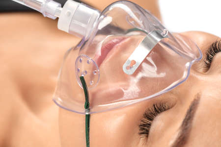 Young beautiful woman with oxygen mask in the hospital.