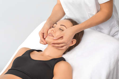 Masseur makes a relaxing massage on the face, neck, shoulders and collarbones of a young beautiful woman in a spa. Cosmetology and massage concept.