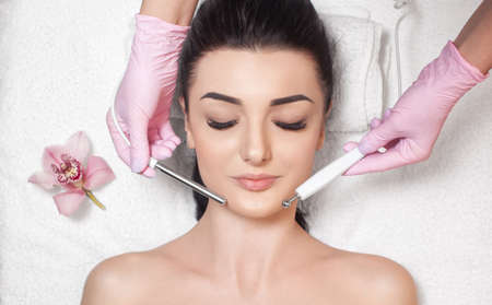 The cosmetologist makes the apparatus a procedure of Microcurrent therapy of a beautiful, young woman in a beauty salon. Cosmetology and professional skin care. Zdjęcie Seryjne