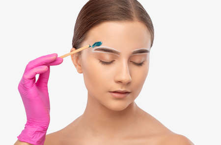 Makeup artist does facial hair removal procedure. Beautiful girl with blue eyes having Permanent Make-up on her Eyebrows. Professional makeup.