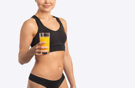 Young slender woman with a beautiful figure in a tracksuit holding a glass of orange juice. The concept of proper nutrition and healthy lifestyle. 版權商用圖片