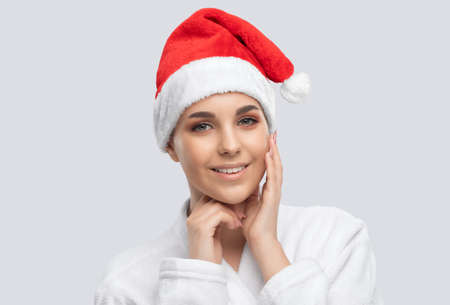 Portrait of a beautiful brunette girl in santa hat with healthy clean skin and fresh make-up. Aesthetic cosmetology and makeup concept.