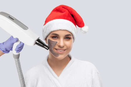 Carbon face peeling procedure in a beauty salon. Girl in santa claus hat. New Year's and Cosmetology concept.