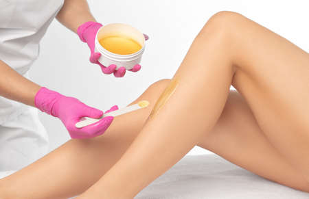 A beautician makes a sugar paste depilation of a woman's legs in a beauty salon. Female aesthetic cosmetology.