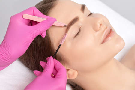 Makeup artist plucks eyebrows in a beauty salon. Professional makeup and cosmetology skin care.