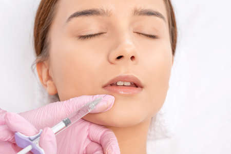 Cosmetologist does injections for lips augmentation and anti wrinkle in the nasolabial folds of a beautiful woman. Women's cosmetology in the beauty salon. Standard-Bild