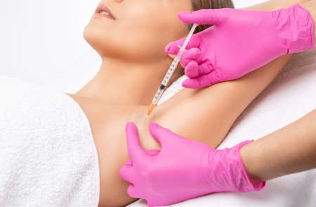 The doctor makes injections of botulinum toxin in the underarm area against hyperhidrosis. Women's cosmetology concept. Stock Photo