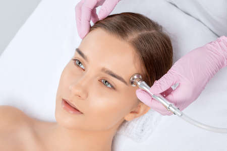 The cosmetologist makes the procedure Microdermabrasion of the face skin of a beautiful girl in a beauty salon. Cosmetology and professional skin care.