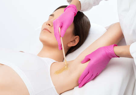A beautician makes a sugar paste depilation under the armpits in a beauty salon. Female aesthetic cosmetology. 写真素材