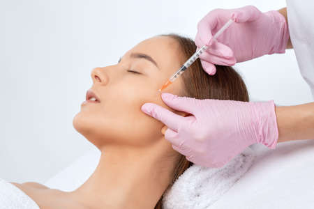 Cosmetologist makes rejuvenating anti wrinkle injections on the face of a beautiful woman. Female aesthetic cosmetology in a beauty salon.