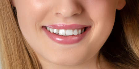 Beautiful young woman smiling. Cosmetic skin care and make-up. Dentistry. Close-up smile.