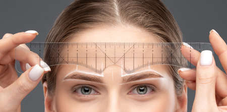 Make-up artist makes markings with white pencil for eyebrow and paints eyebrows. Professional makeup and facial care.
