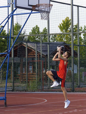 Boy playing basketball, jump and shot photo