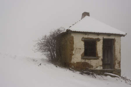 Old house in the fog in winter