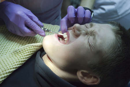 A young boy getting his teeth examined and cleaned Stock Photo