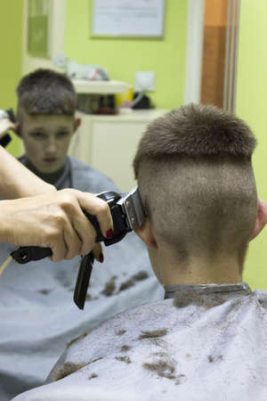 Barber cutting hair with electric razor photo