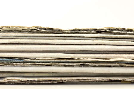 Newspaper headlines shown side on in a stack of newspaper photo