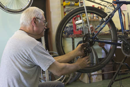 Man repairing bicycles in workshop photo