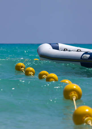 Boat and a buoy floating on the sea photo