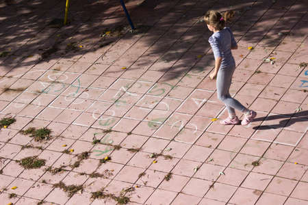 hopscotch: Girl playing hopscotch on the playground