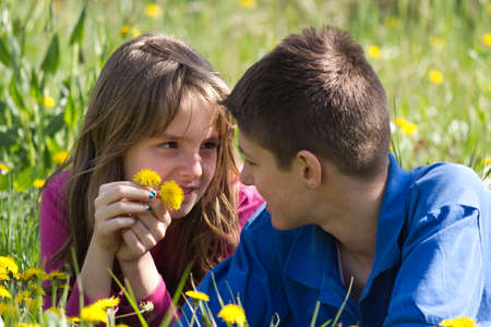 Boy and girl enjoying in the nature .They lie in a field surrounded by dandelion. photo