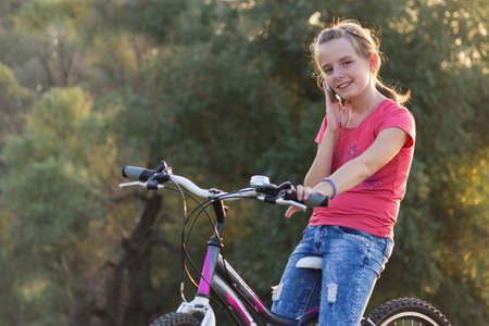 prety: Girl speaks on a mobile phone while sitting on bicycles in the countryside