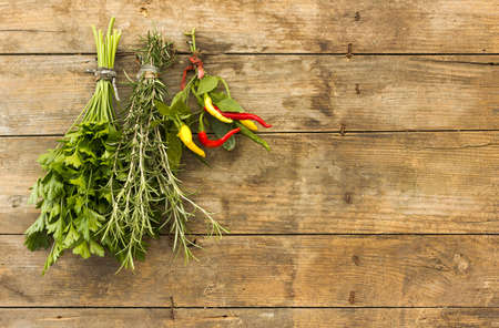 tied down: Bunches herbs hanging on a wooden board