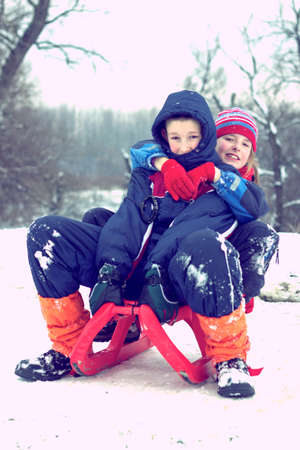 snows: Boy and girl on a sleigh, enjoy the winter activities